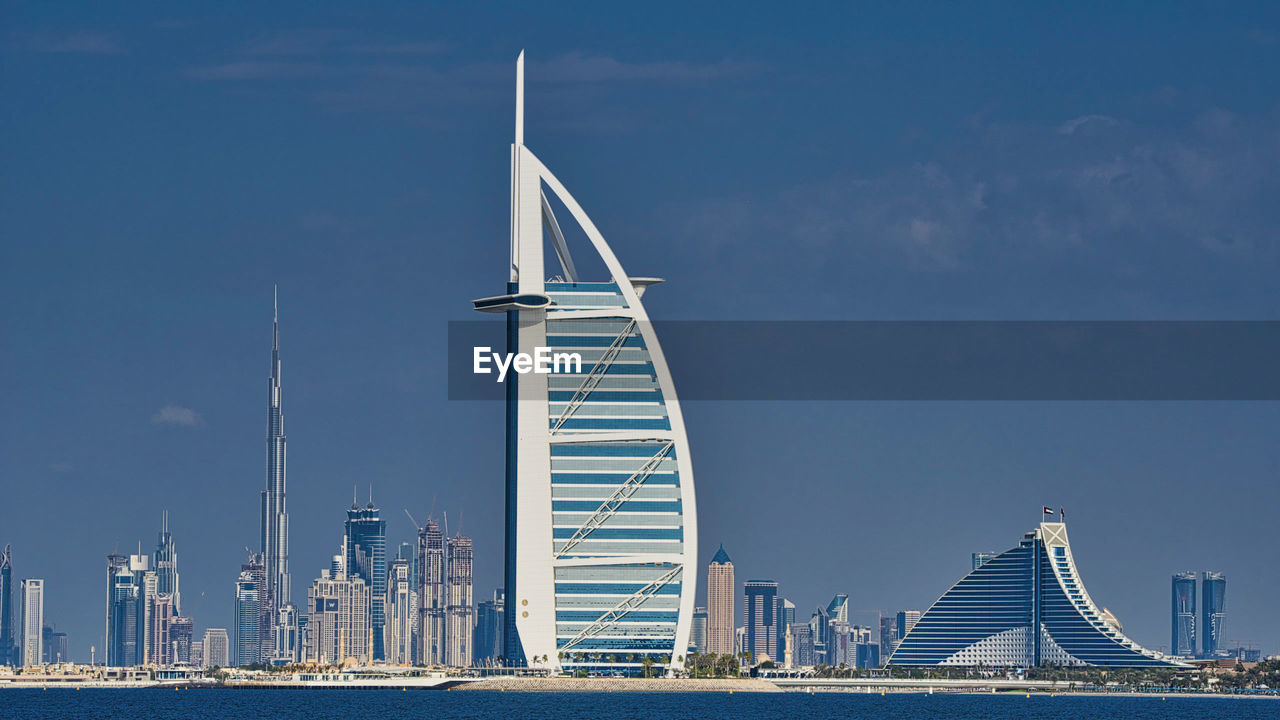 architecture, sky, built structure, building exterior, transportation, water, city, modern, office building exterior, connection, nature, travel destinations, skyscraper, waterfront, travel, no people, bridge, bridge - man made structure, cable-stayed bridge, outdoors, cityscape, sailboat, financial district, luxury, bay, spire