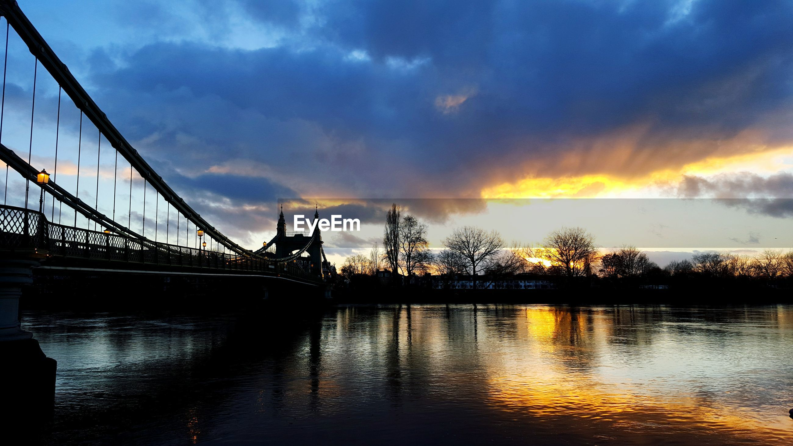 Hammersmith bridge over thames river against cloudy sky during sunset