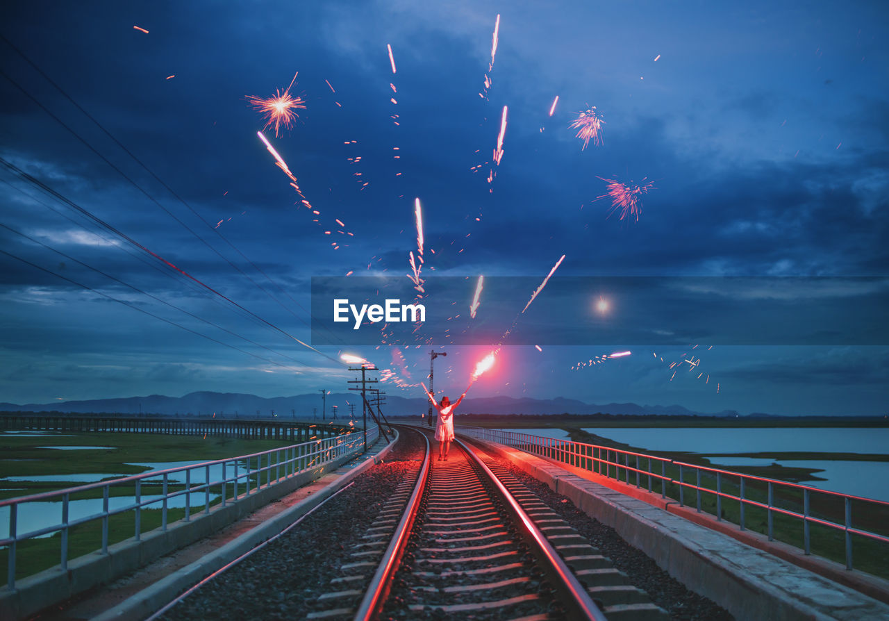 Full length of woman holding firework while standing on railroad track against sky