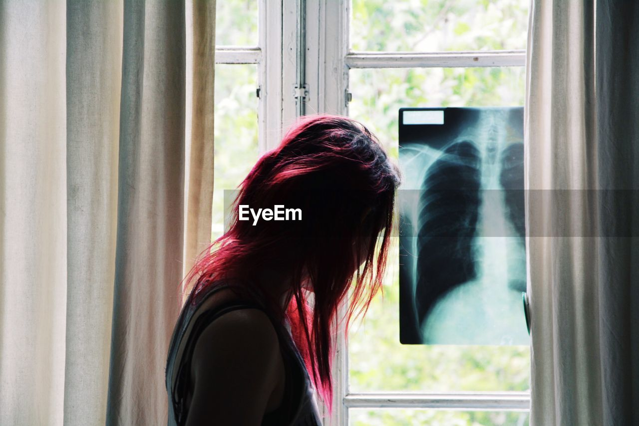 Side View Of Woman With Dyed Hair Standing By X-Ray On Window At Home