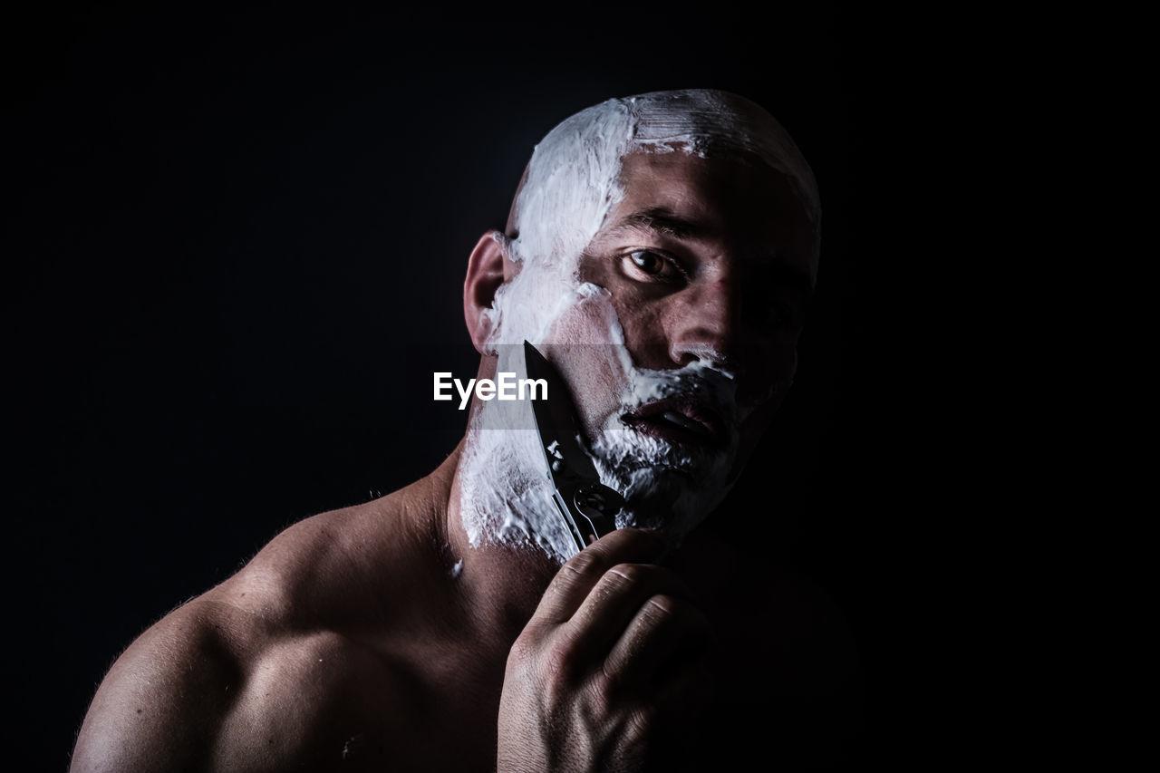 Man Shaving With Knife Against Black Background