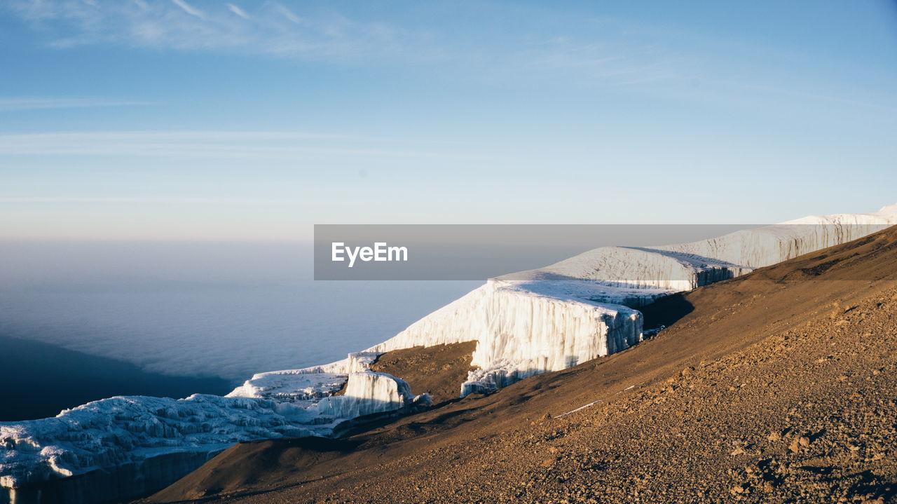 Snow On Mountain By Sea Against Sky
