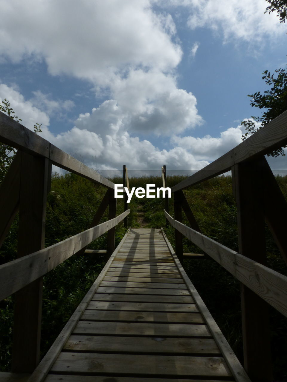 sky, cloud - sky, railing, direction, the way forward, nature, architecture, built structure, day, bridge, diminishing perspective, connection, plant, tree, land, wood - material, no people, footbridge, outdoors, bridge - man made structure, long