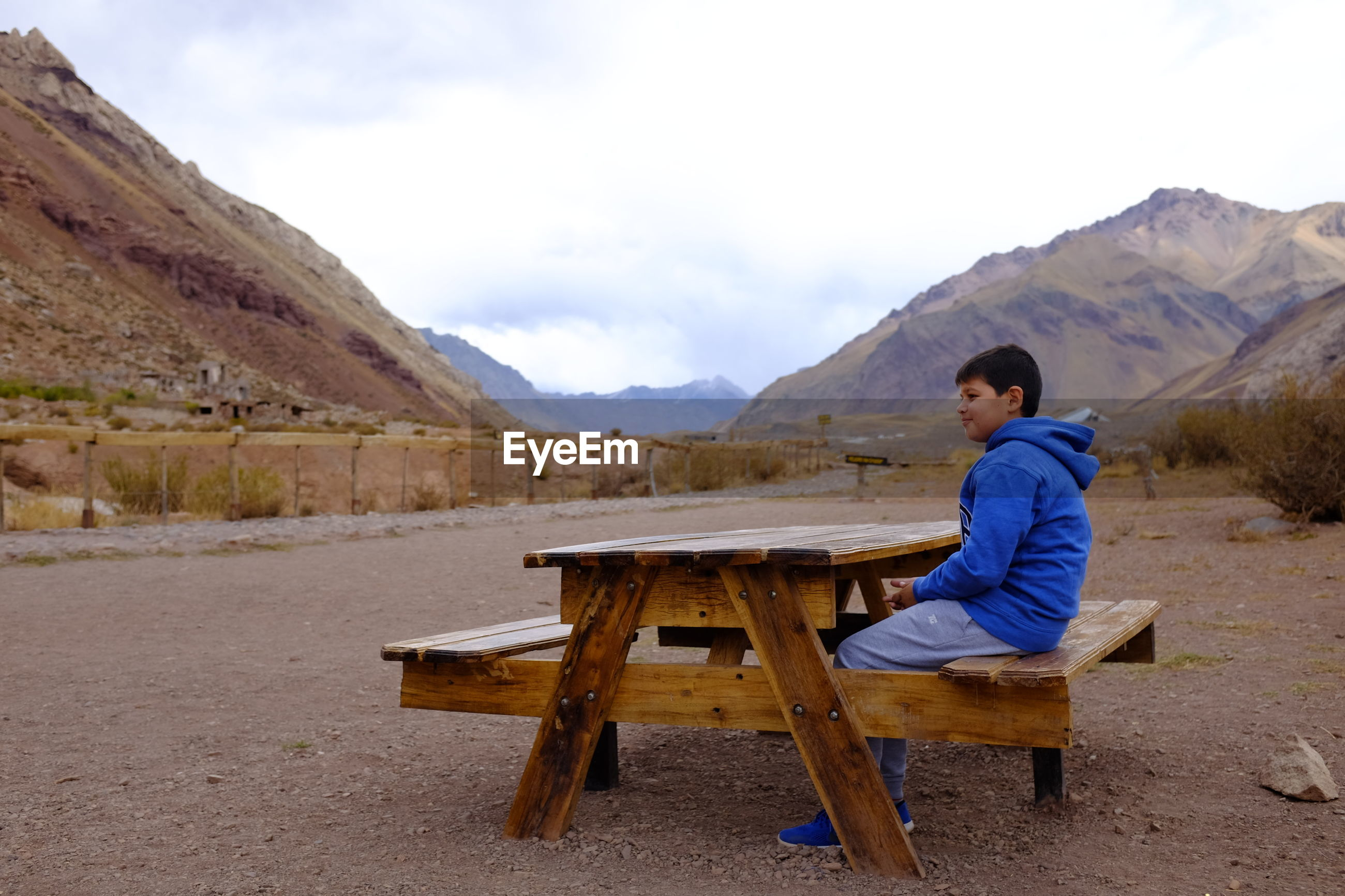 Boy looking away while sitting on seat against mountains