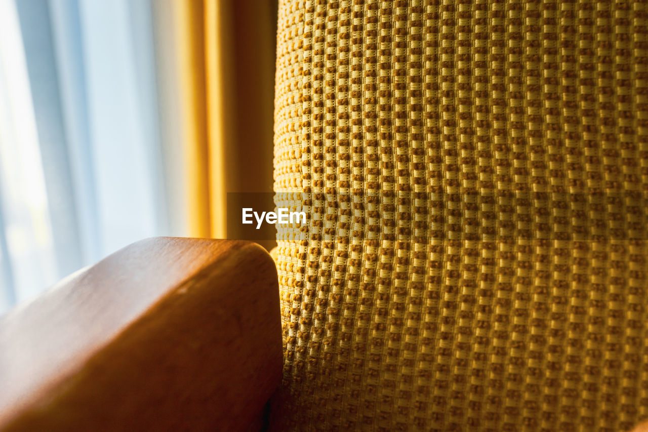 close-up, indoors, no people, curtain, pattern, seat, textile, focus on foreground, textured, window, still life, chair, selective focus, table, home interior, yellow, design, detail, shape, day