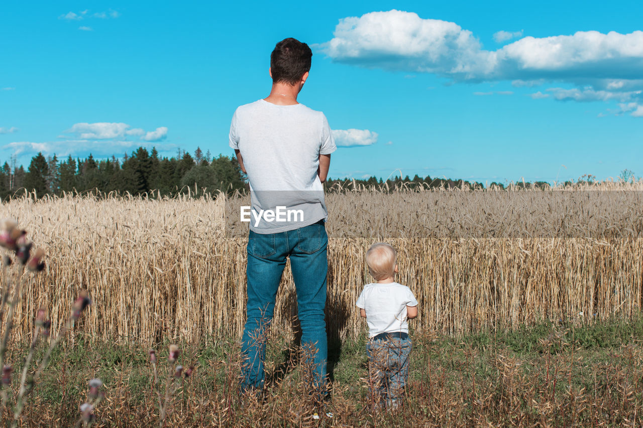 Rear View Of Father With Son Standing On Field Against Sky