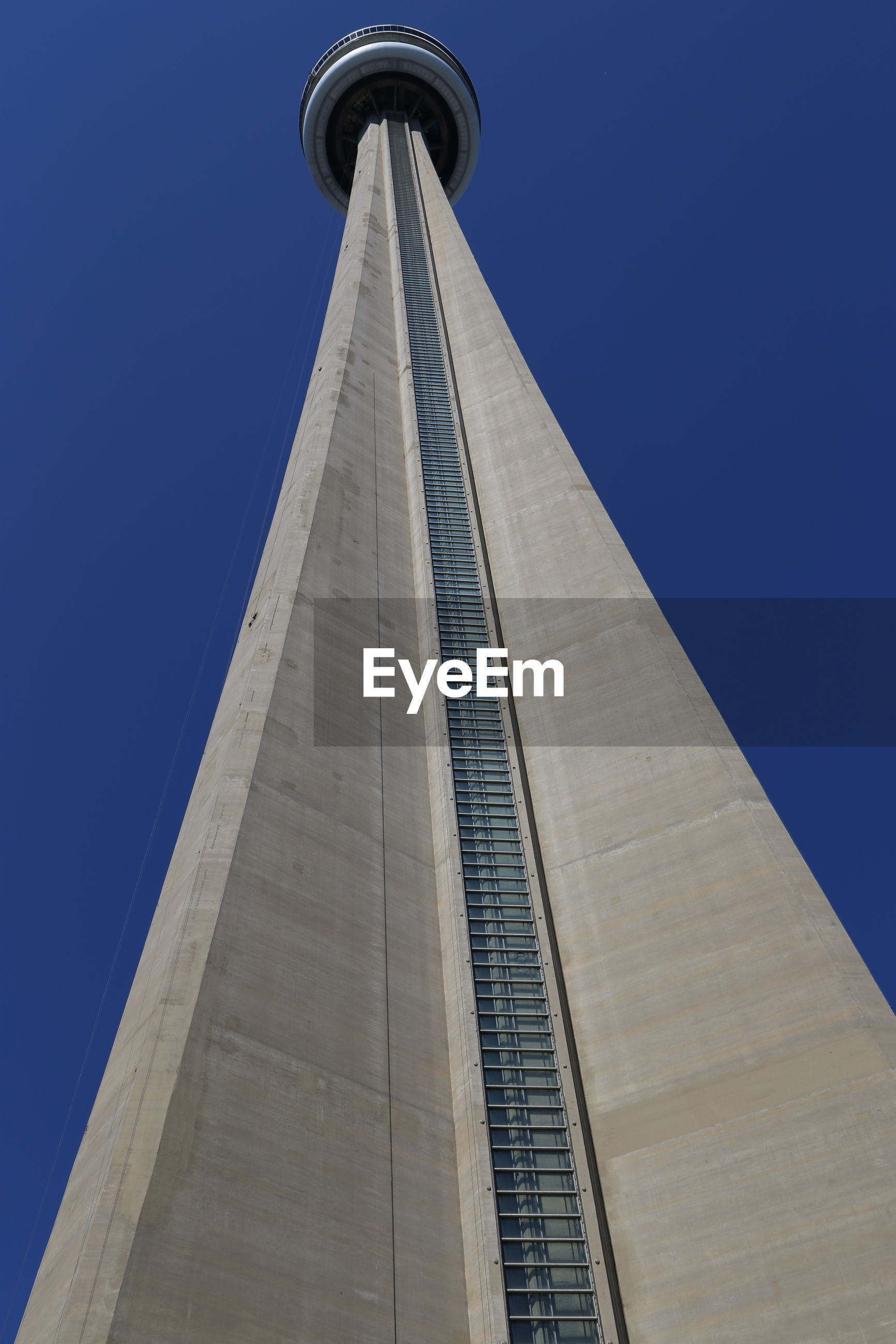 Low angle view of tower in city against blue sky