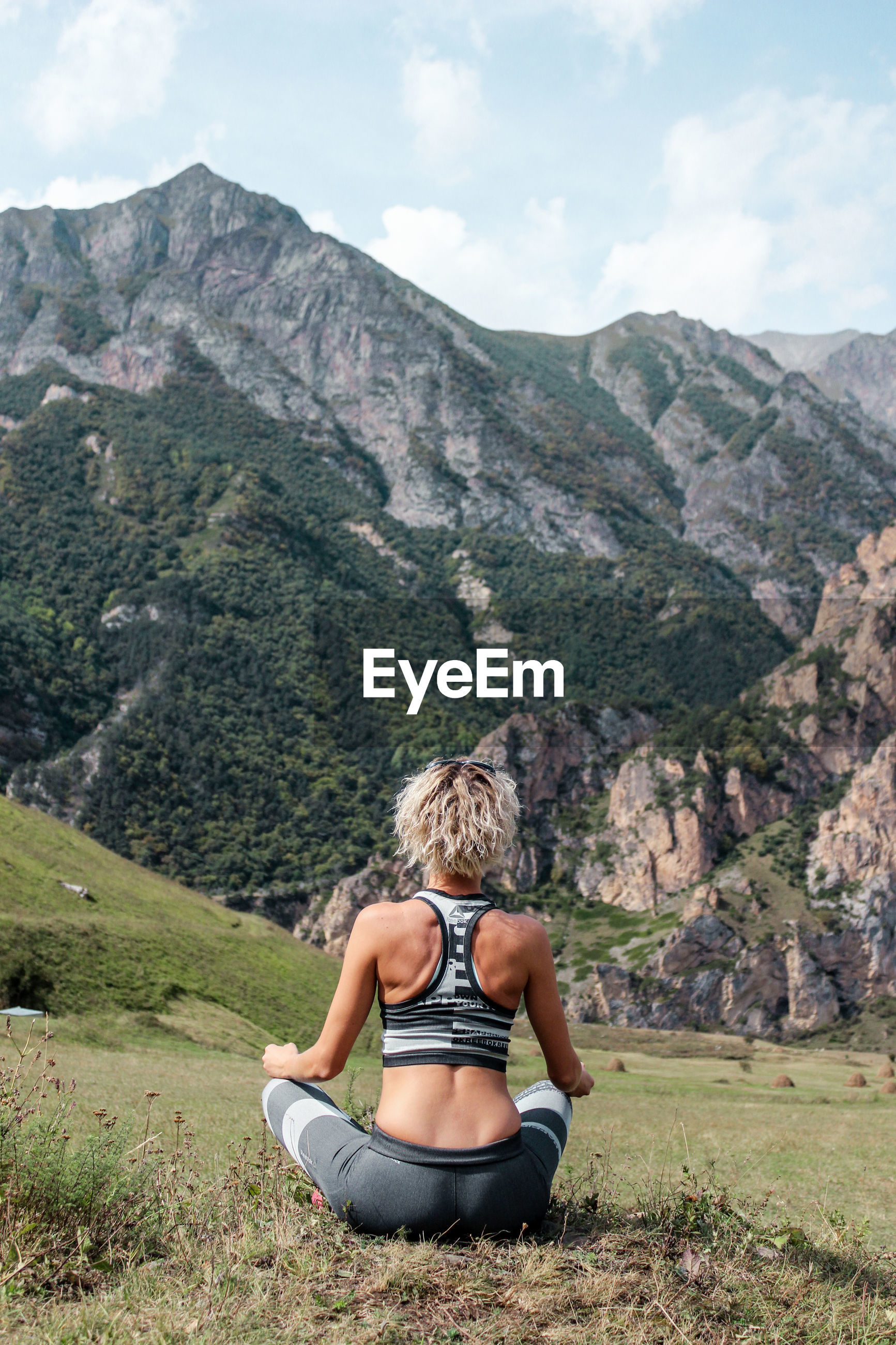 Full length rear view of woman exercising on mountain
