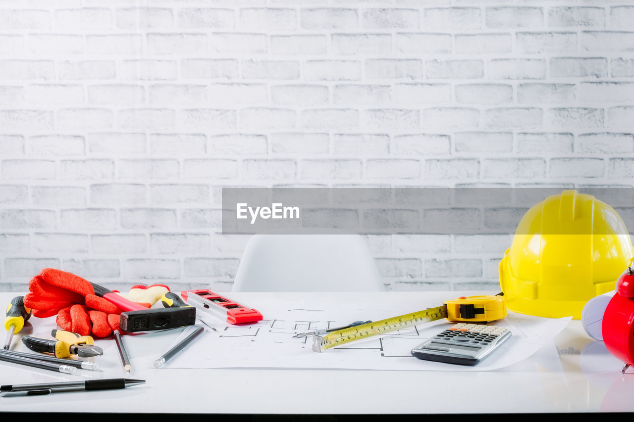 indoors, no people, brick wall, wall - building feature, table, brick, wall, yellow, white color, still life, hardhat, headwear, hat, large group of objects, copy space, domestic room, red, preparation, paper, close-up, blueprint, electric lamp