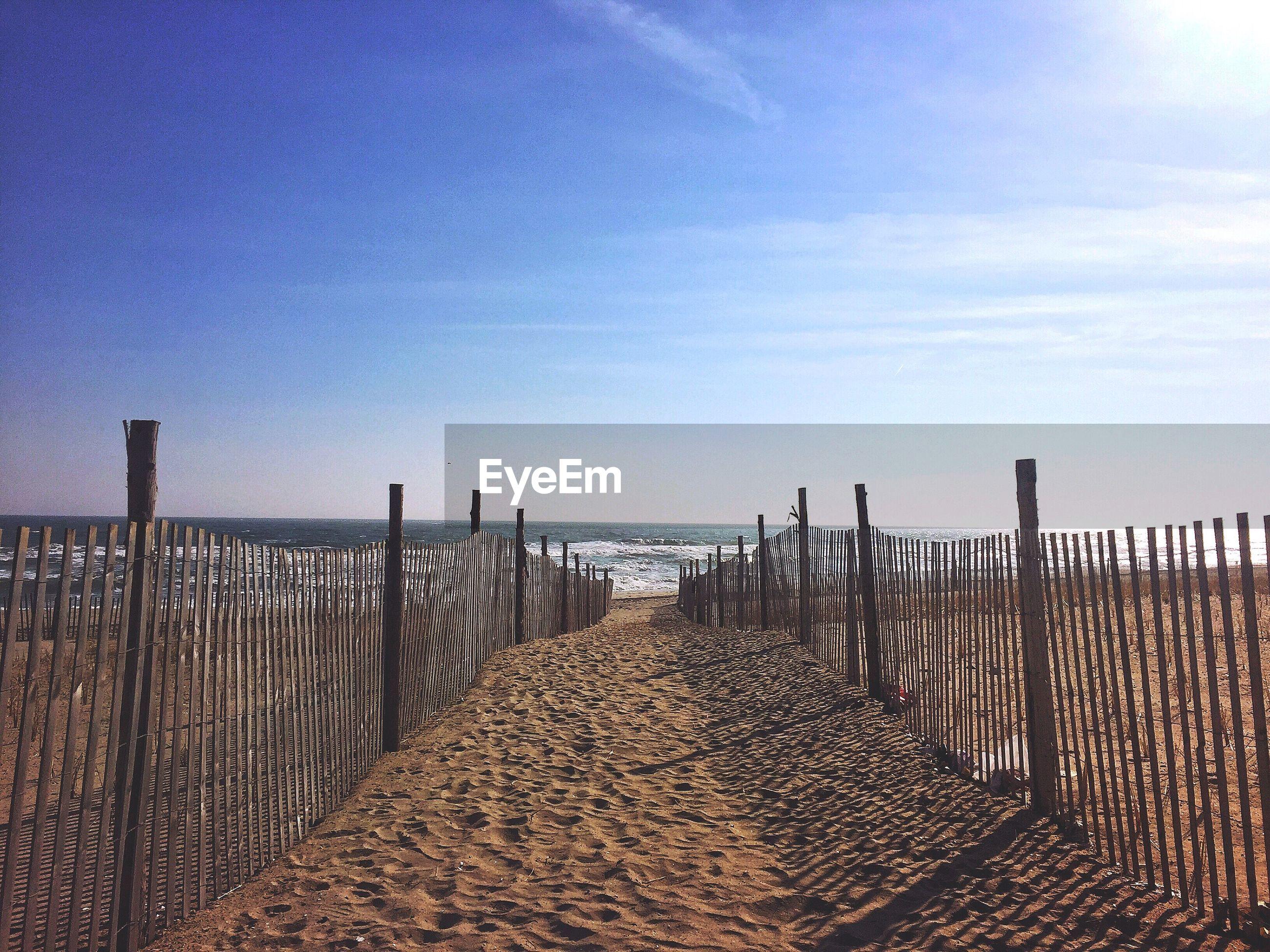 Railing at beach against sky