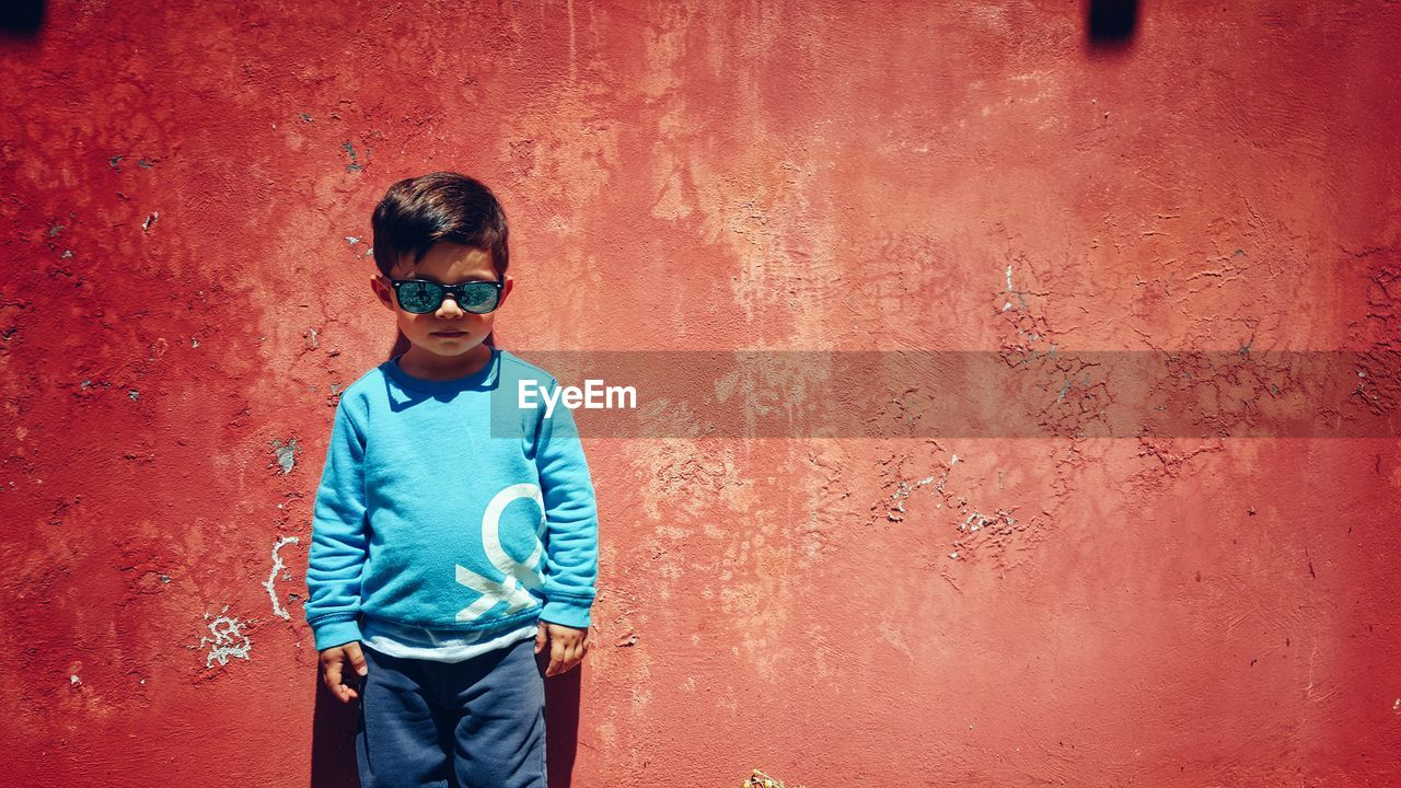 Portrait Of A Young Boy Against Red Wall