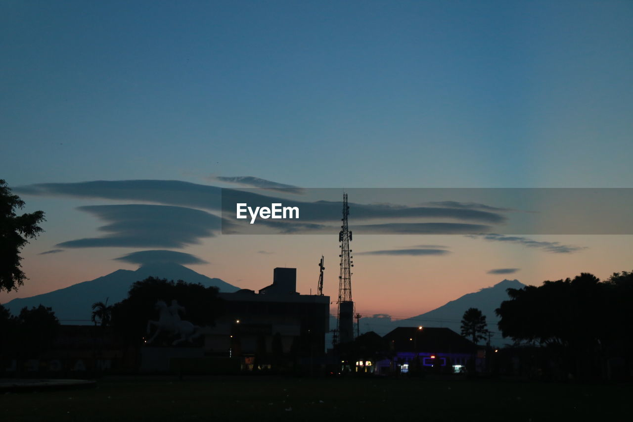 sky, architecture, building exterior, built structure, silhouette, tower, tree, nature, city, sunset, building, no people, industry, tall - high, plant, copy space, dusk, cloud - sky, factory, spire, pollution, skyscraper, air pollution