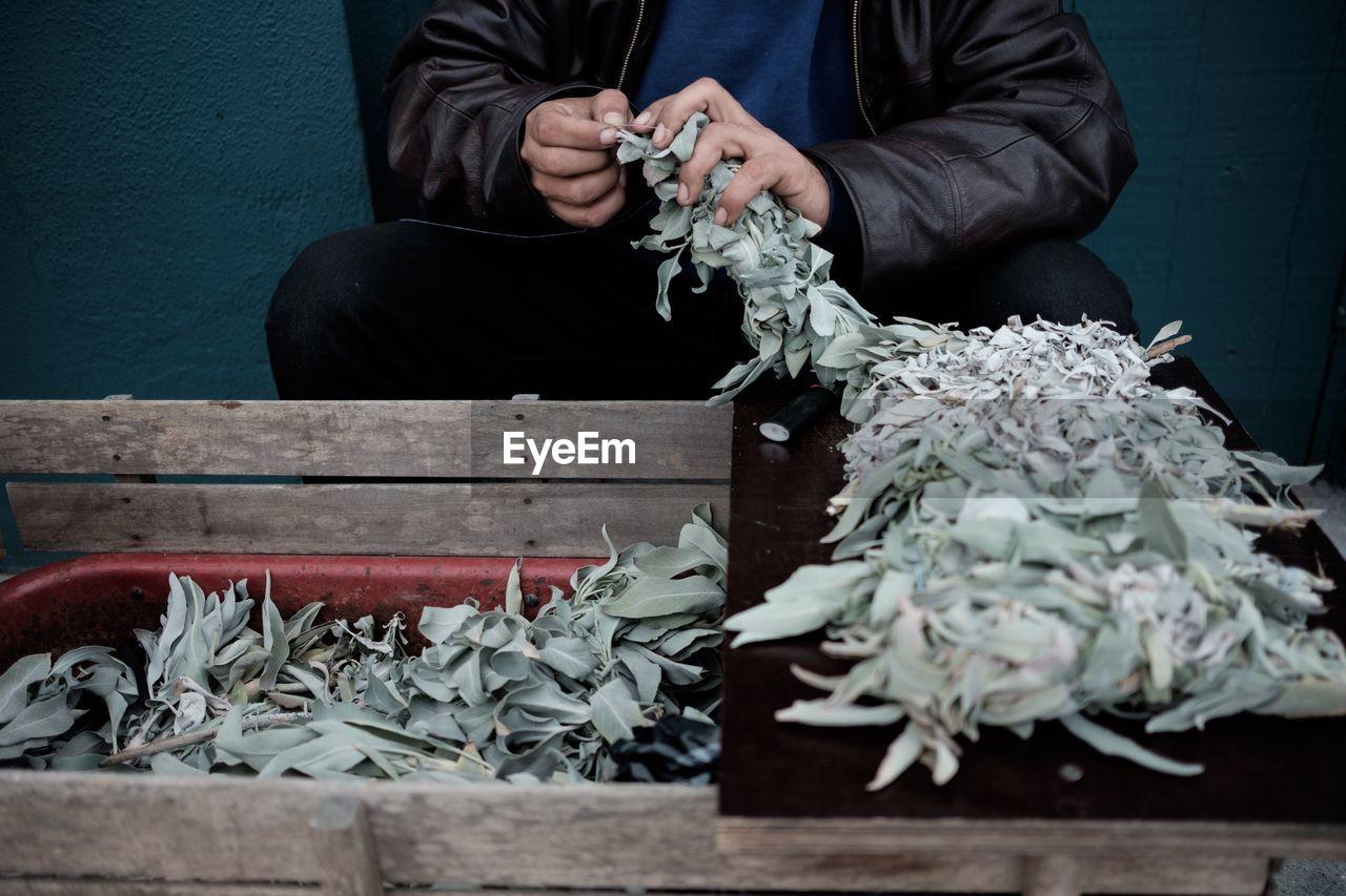Midsection Of Vendor Holding Leaf Vegetables At Market Stall