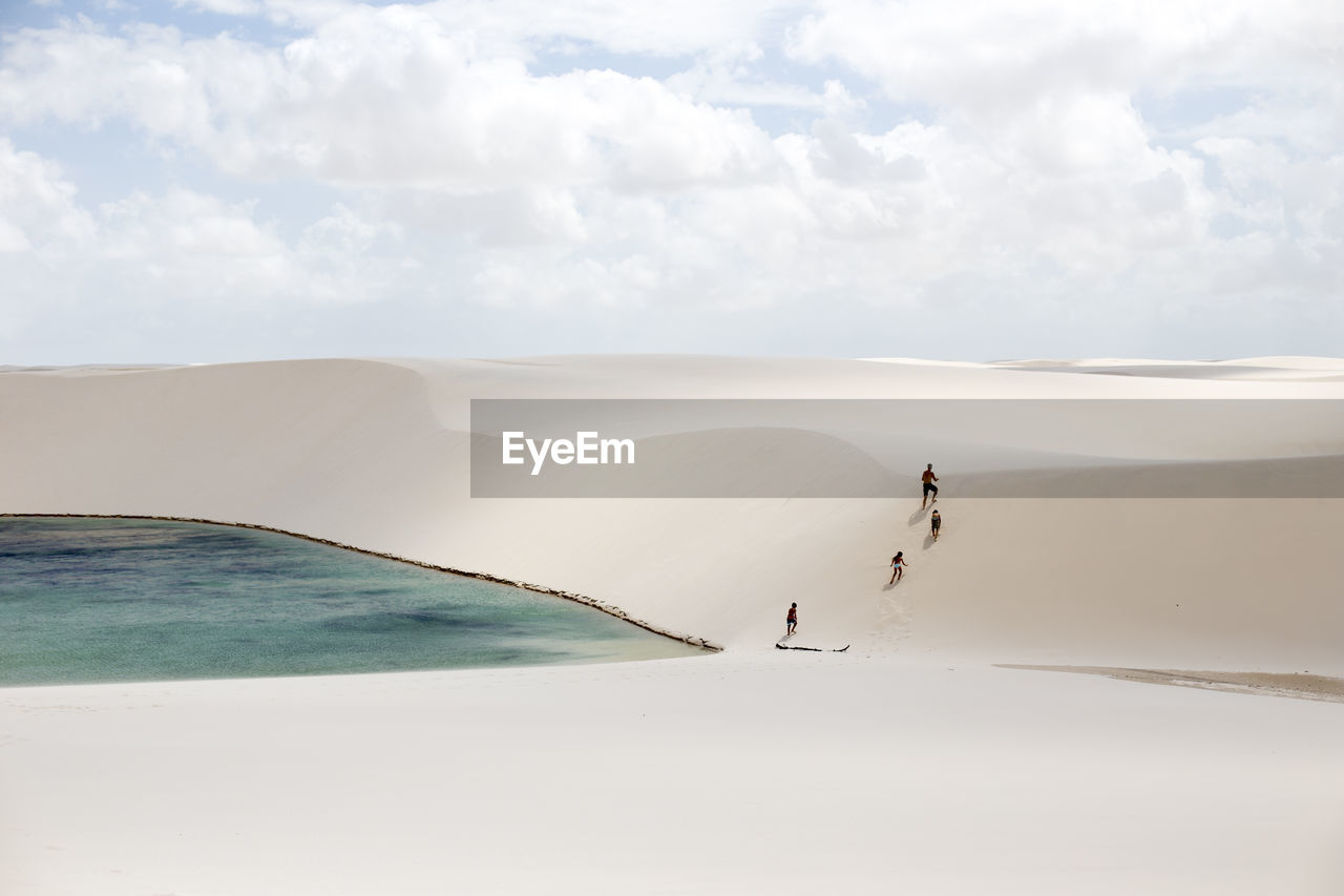 Rear view of people walking on sand dune by lake against sky