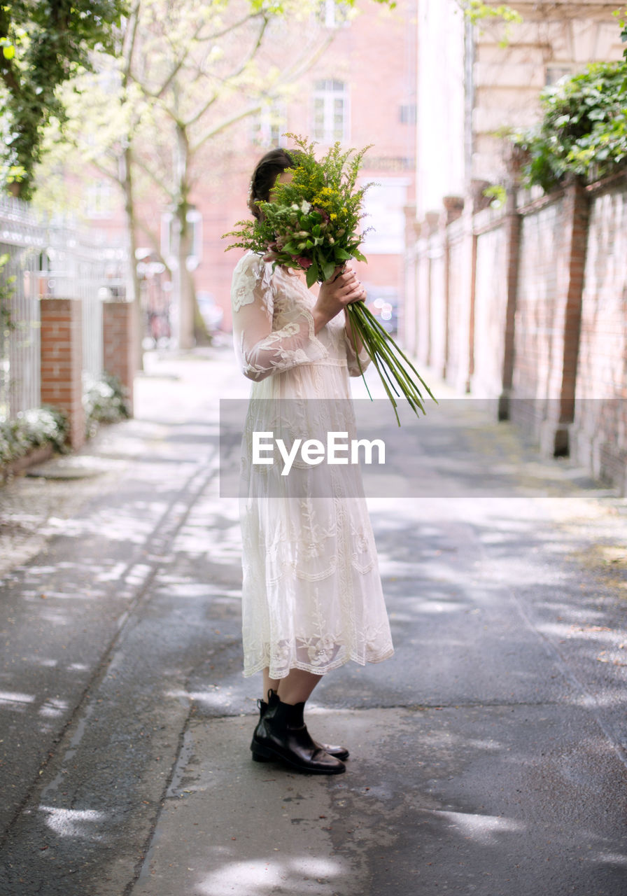 Side View Of Bride Holding Bouquet While Standing On Street