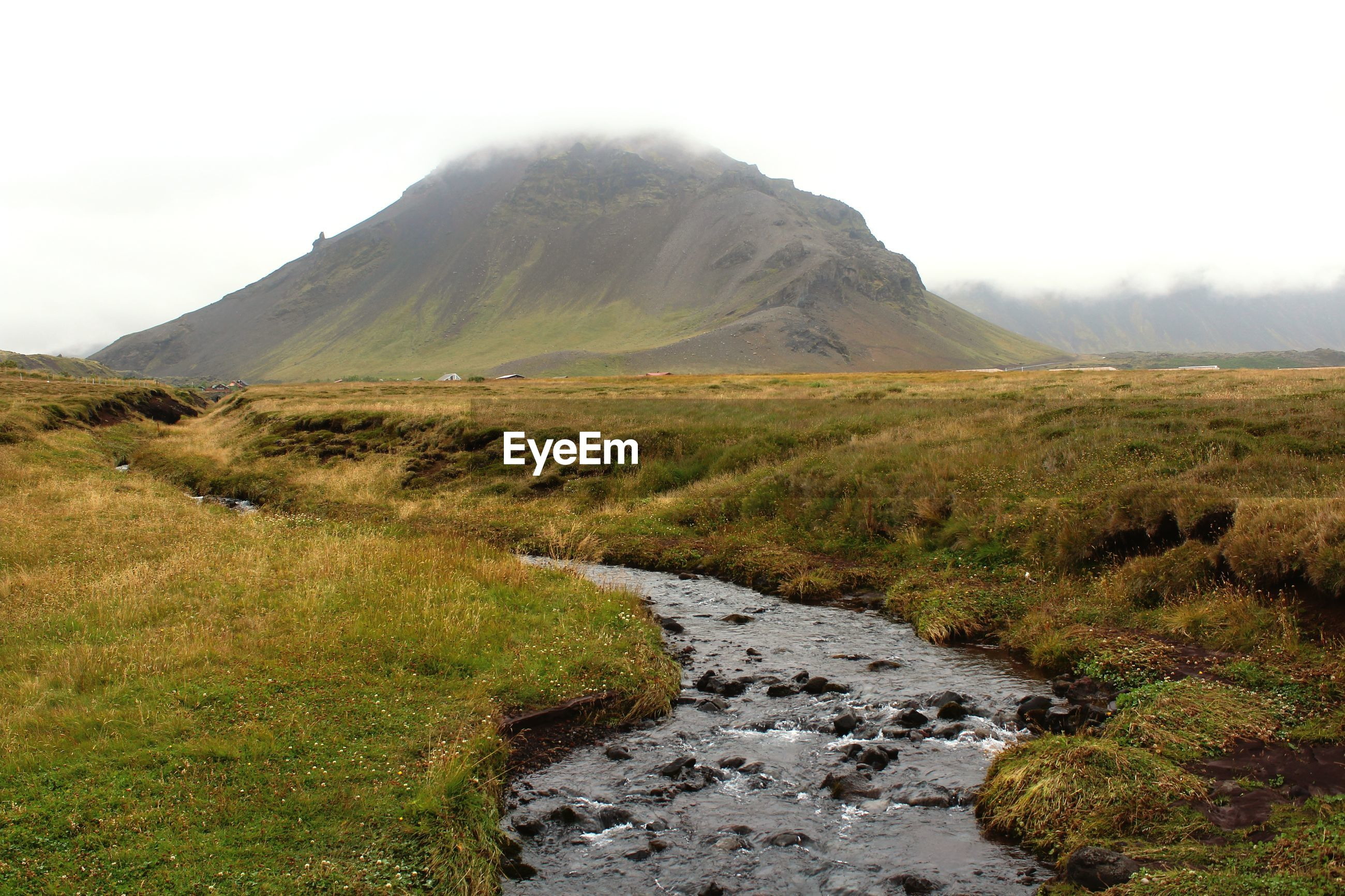 SCENIC VIEW OF STREAM FLOWING BY LAND AGAINST SKY