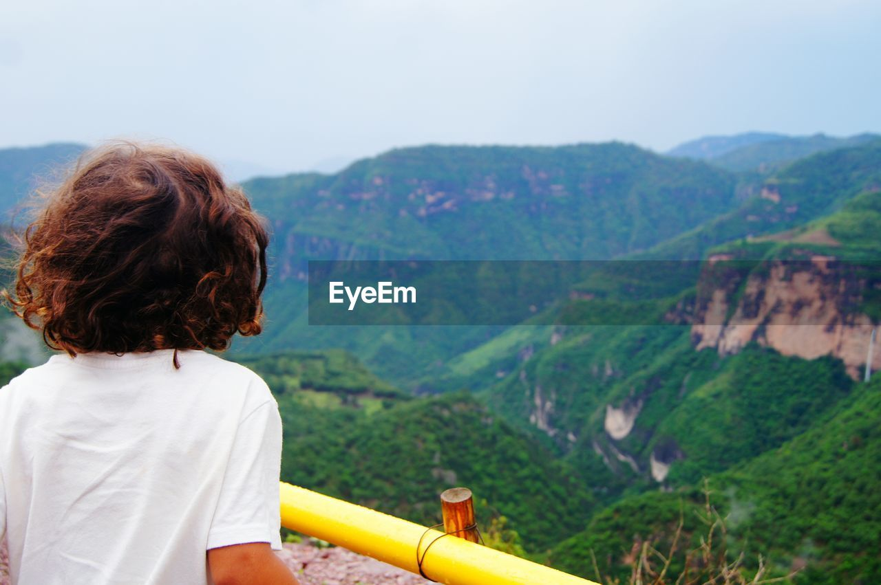 Rear view of boy looking at mountain against clear sky
