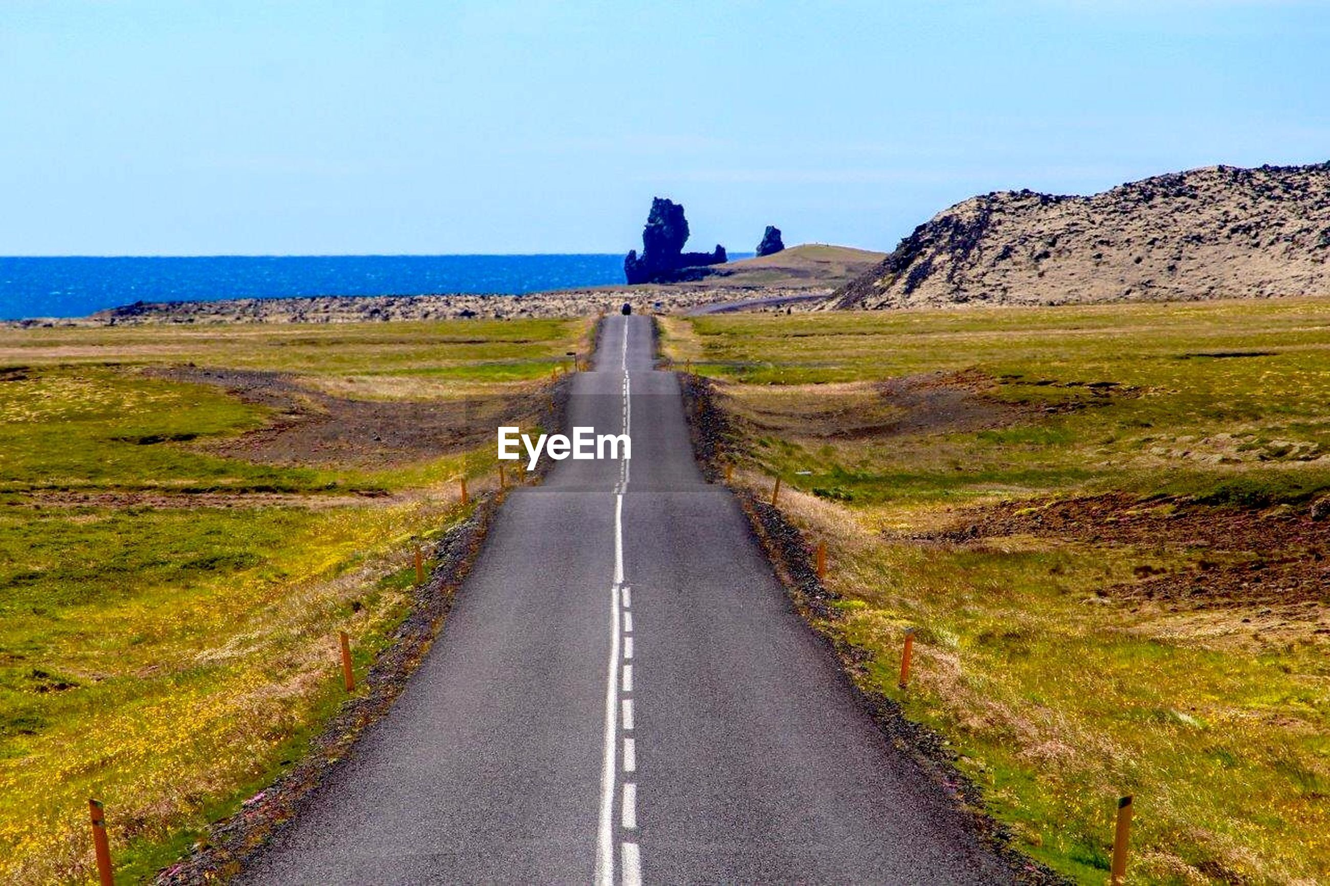 High angle view of road leading towards sea against clear sky