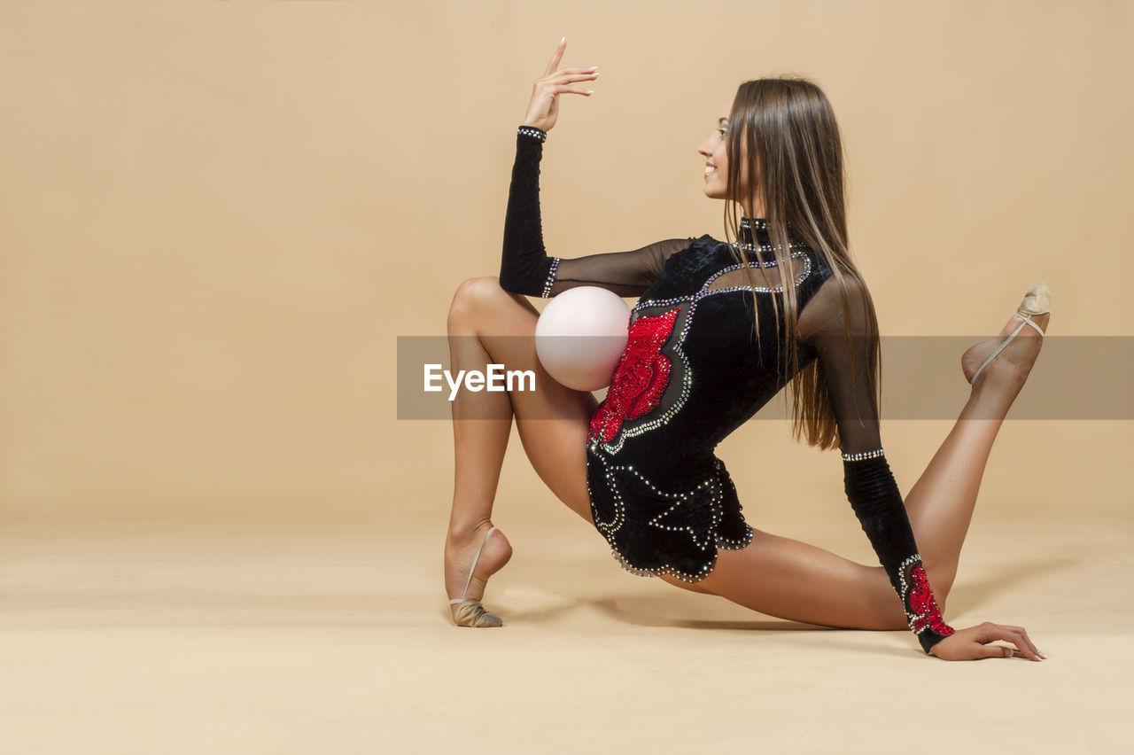 Full length of young woman exercising on beige background
