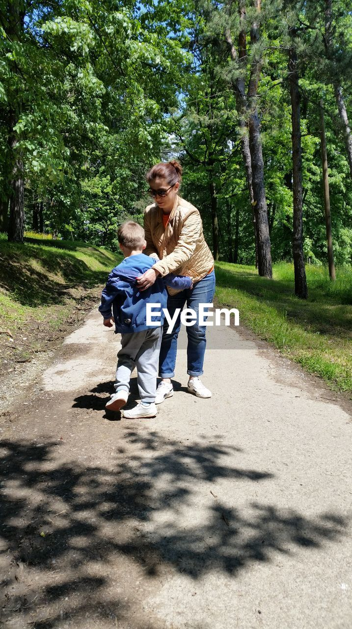 tree, two people, real people, plant, men, full length, casual clothing, togetherness, males, sunlight, bonding, nature, leisure activity, child, shadow, childhood, family, day, emotion, mid adult, positive emotion, son, daughter, outdoors