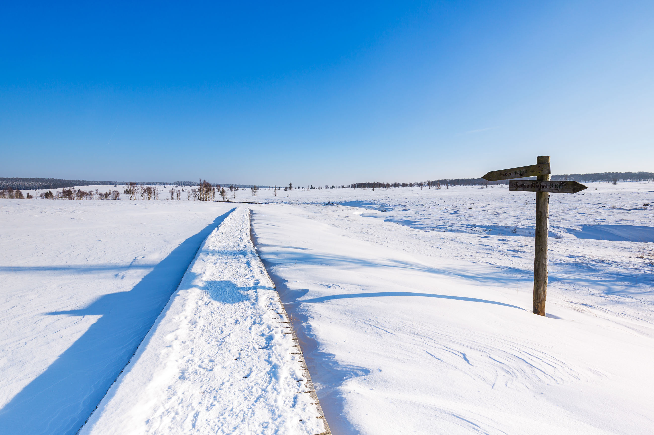 SNOW COVERED FIELD AGAINST CLEAR BLUE SKY