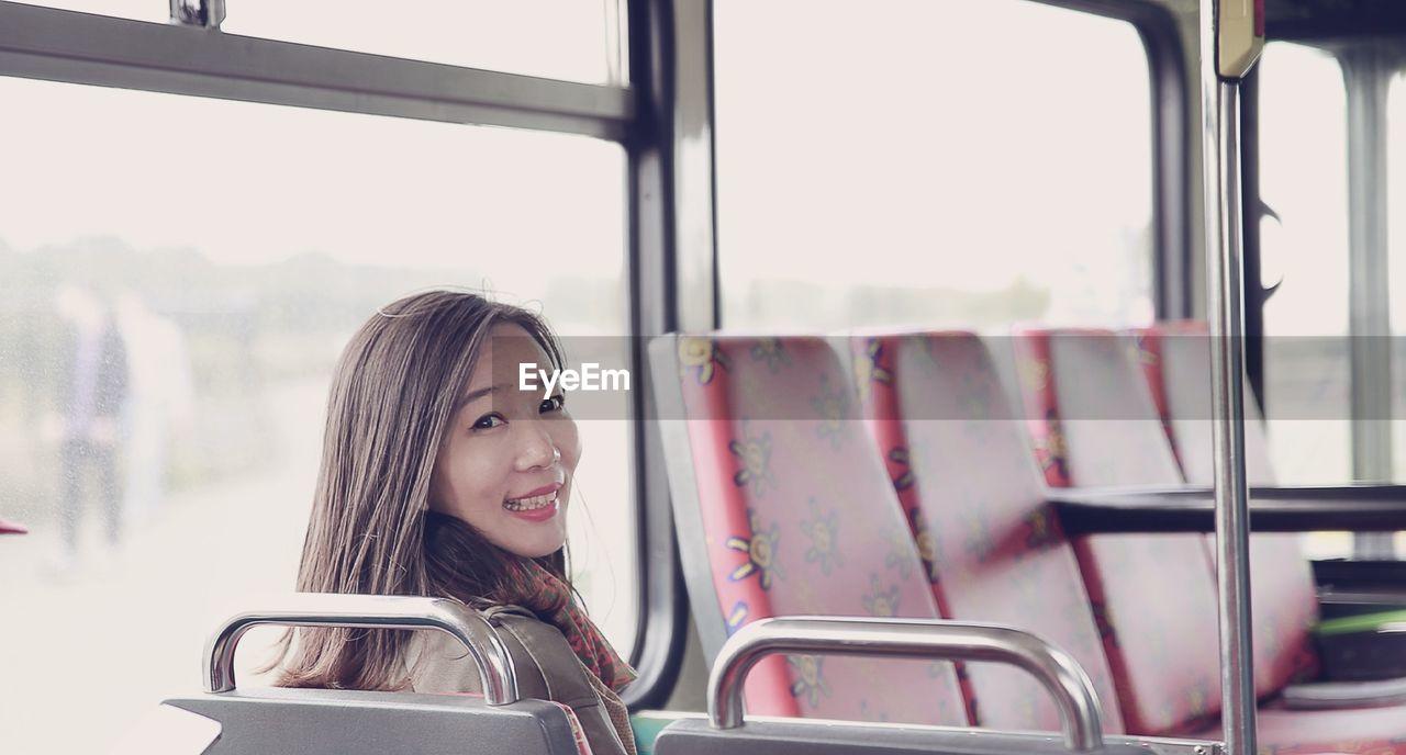 Portrait of happy commuter sitting in bus