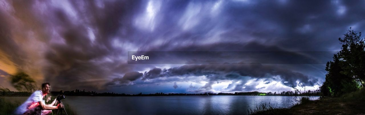PANORAMIC VIEW OF LAKE AGAINST STORM CLOUDS