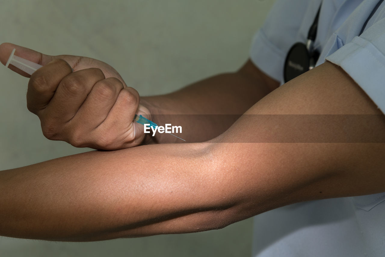 Midsection Of Doctor Injecting Arm