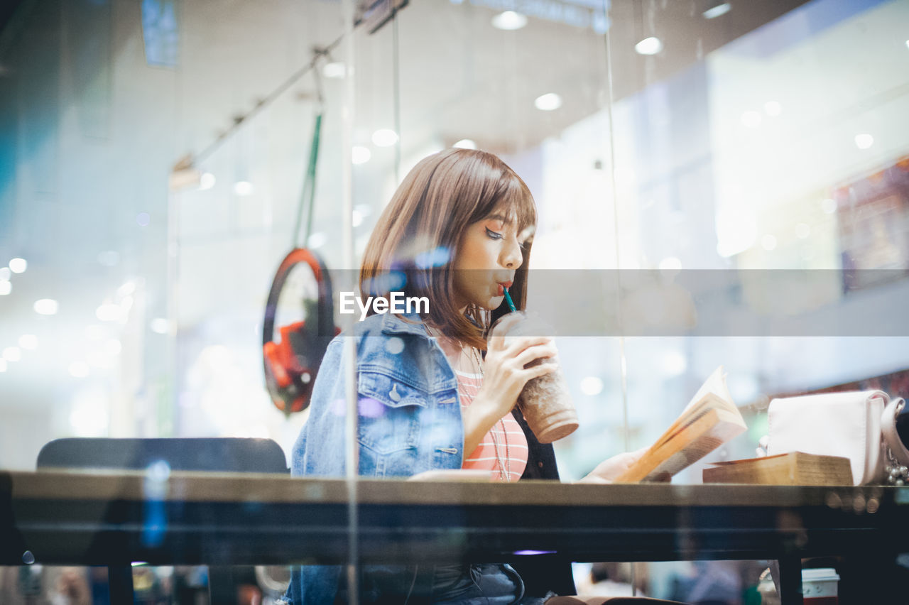 Young Woman Drinking Cold Coffee Seen Through Window