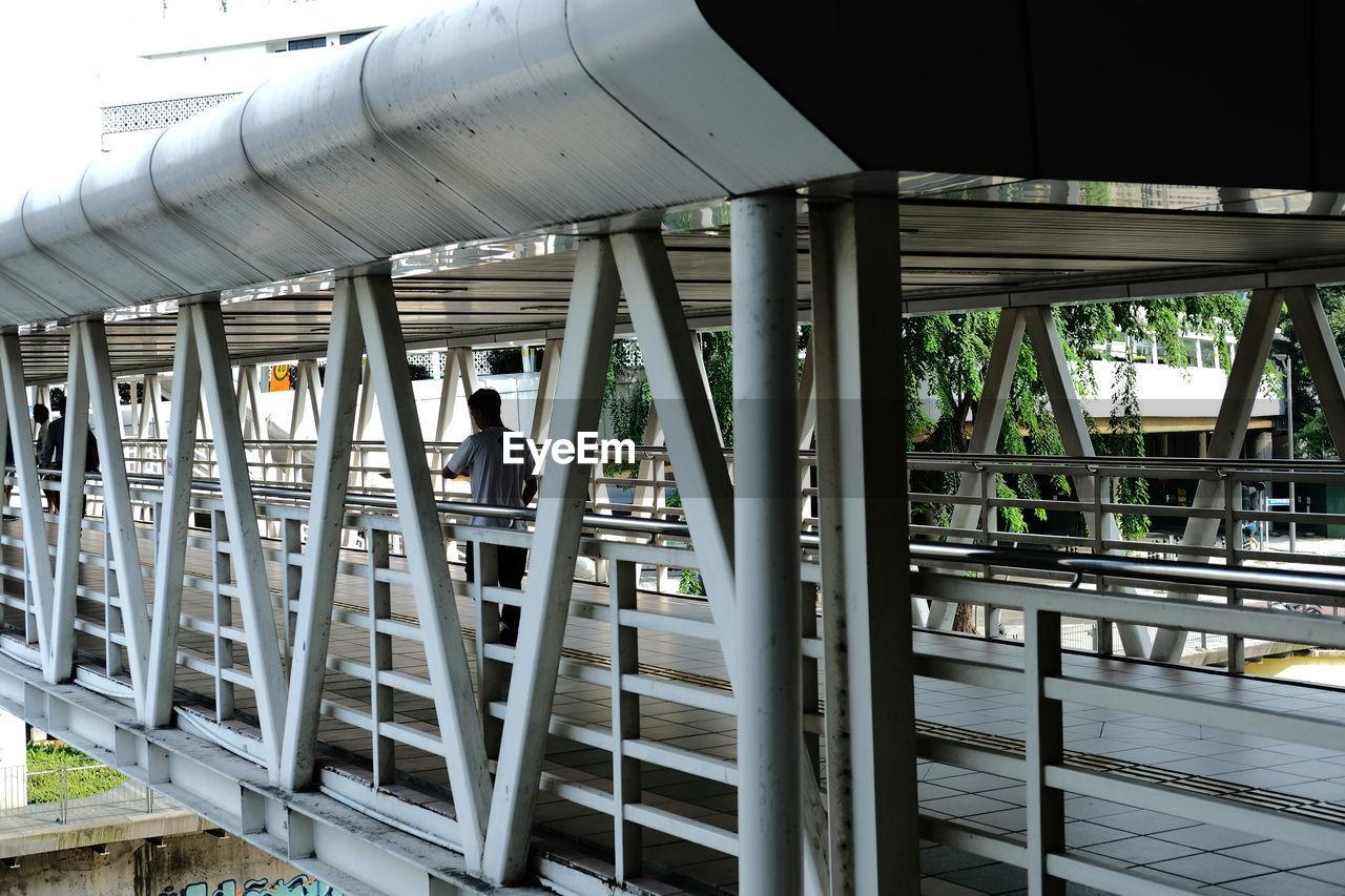 LOW ANGLE VIEW OF METAL BRIDGE OVER RAILWAY STATION