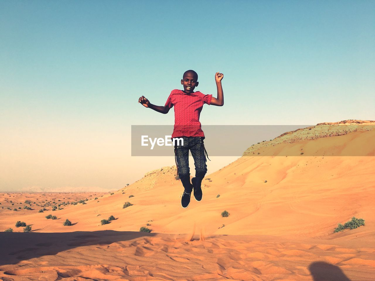 Portrait of boy jumping over sand against sky