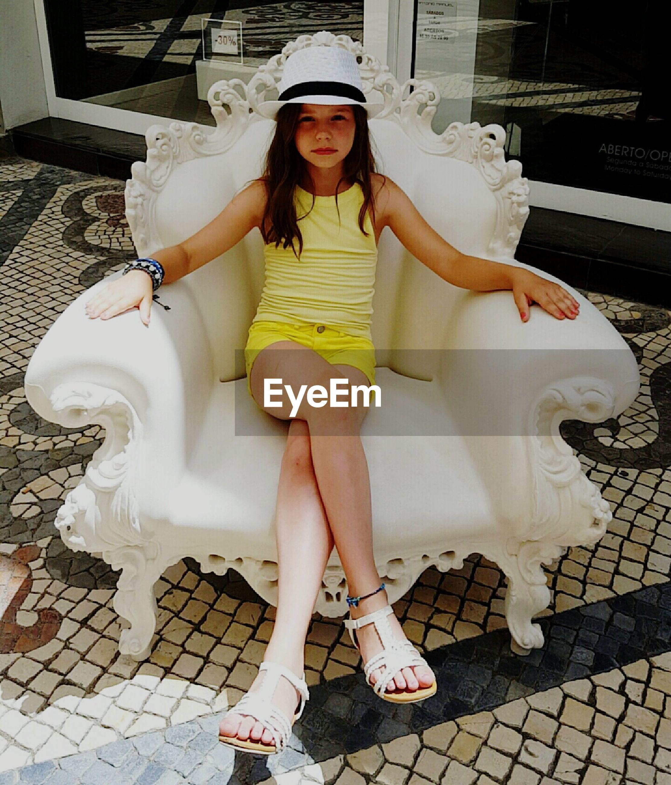 Portrait of girl sitting on armchair on floor