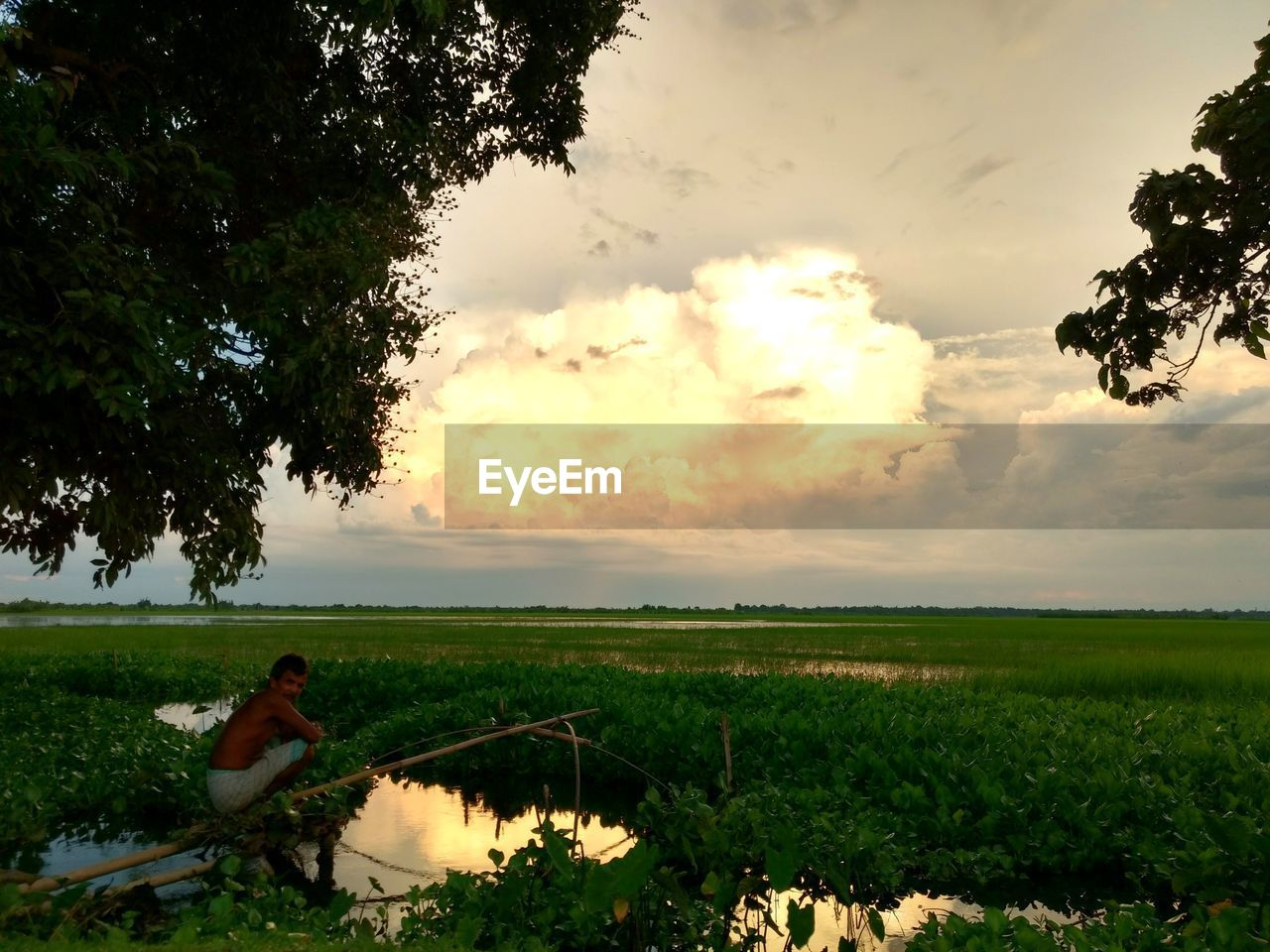 growth, tree, agriculture, nature, field, sky, farm, one person, sunset, real people, outdoors, plant, cloud - sky, rural scene, beauty in nature, full length, landscape, farmer, scenics, men, day, grass, lifestyles, farm worker, women, domestic animals, water, mammal, young adult, people