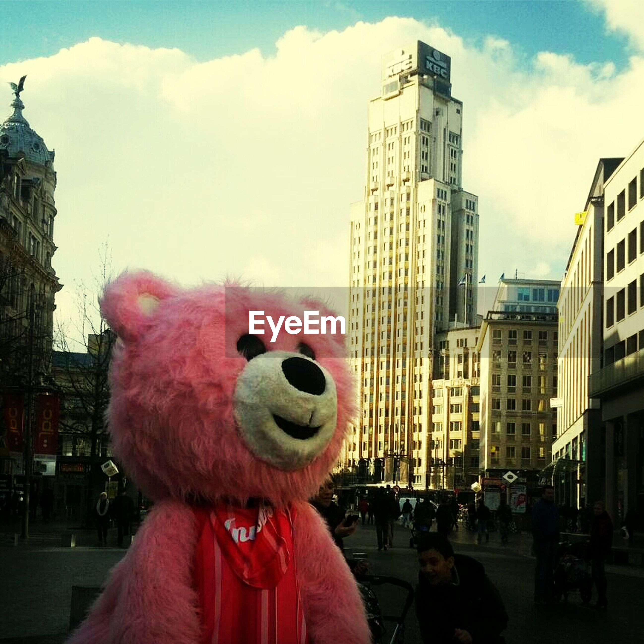 Large pink teddy bear on the road against buildings