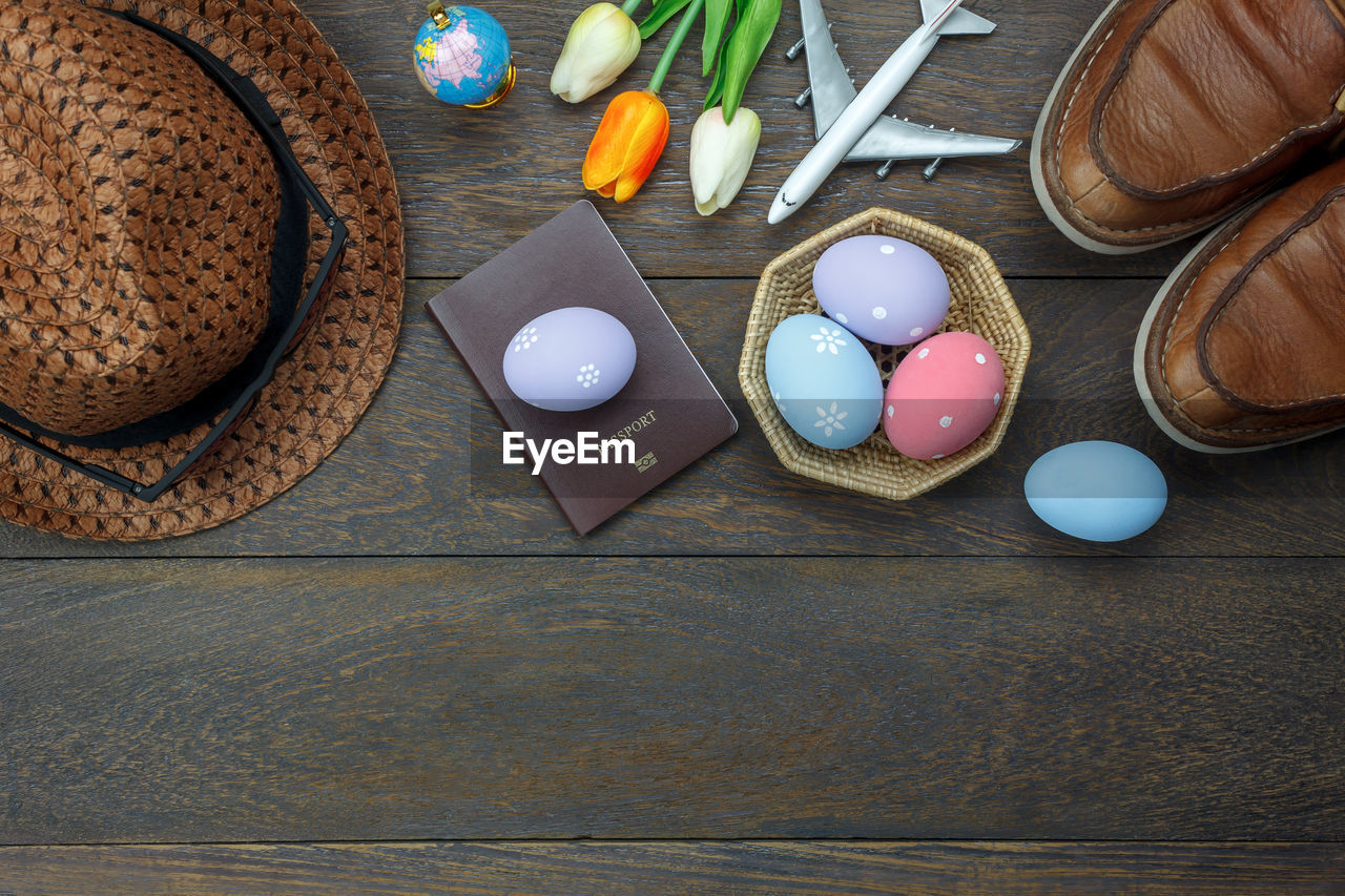 Directly Above View Of Easter Eggs Amidst Passport By Flowers And Hat
