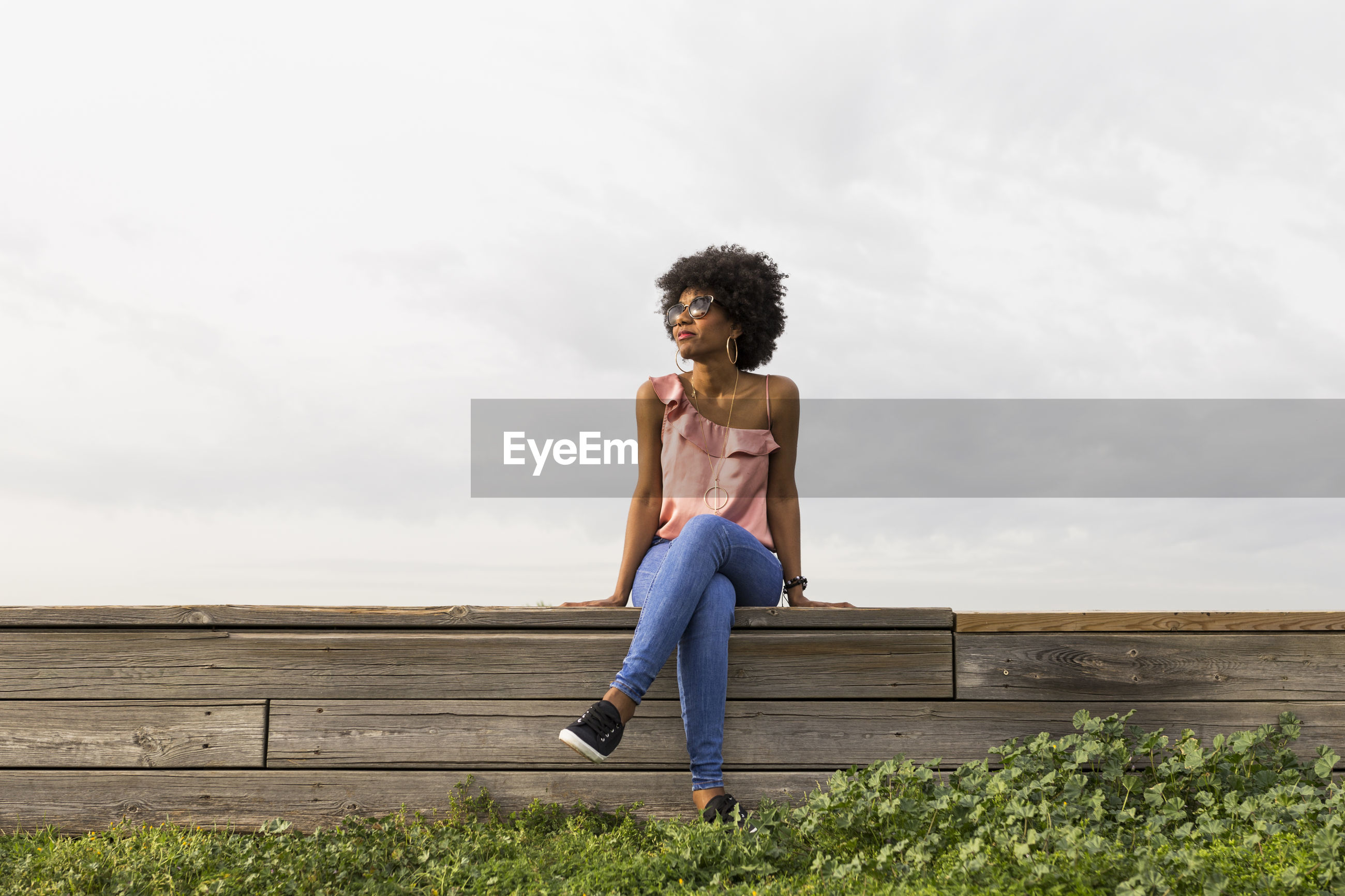 Smiling woman sitting outdoors against sky