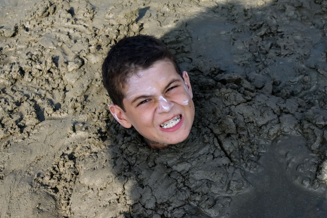 Portrait of boy buried in sand at beach