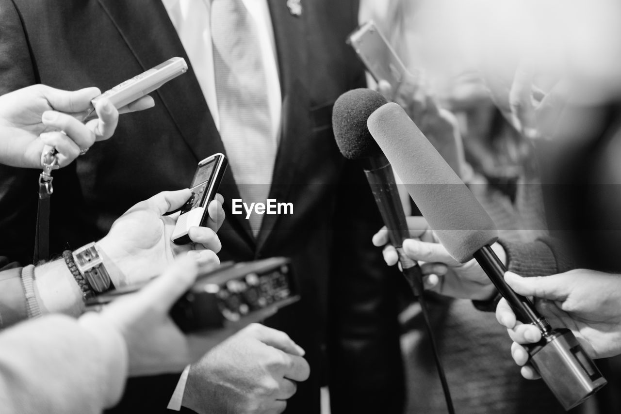 Cropped Hands Of Journalists Interviewing Businessman