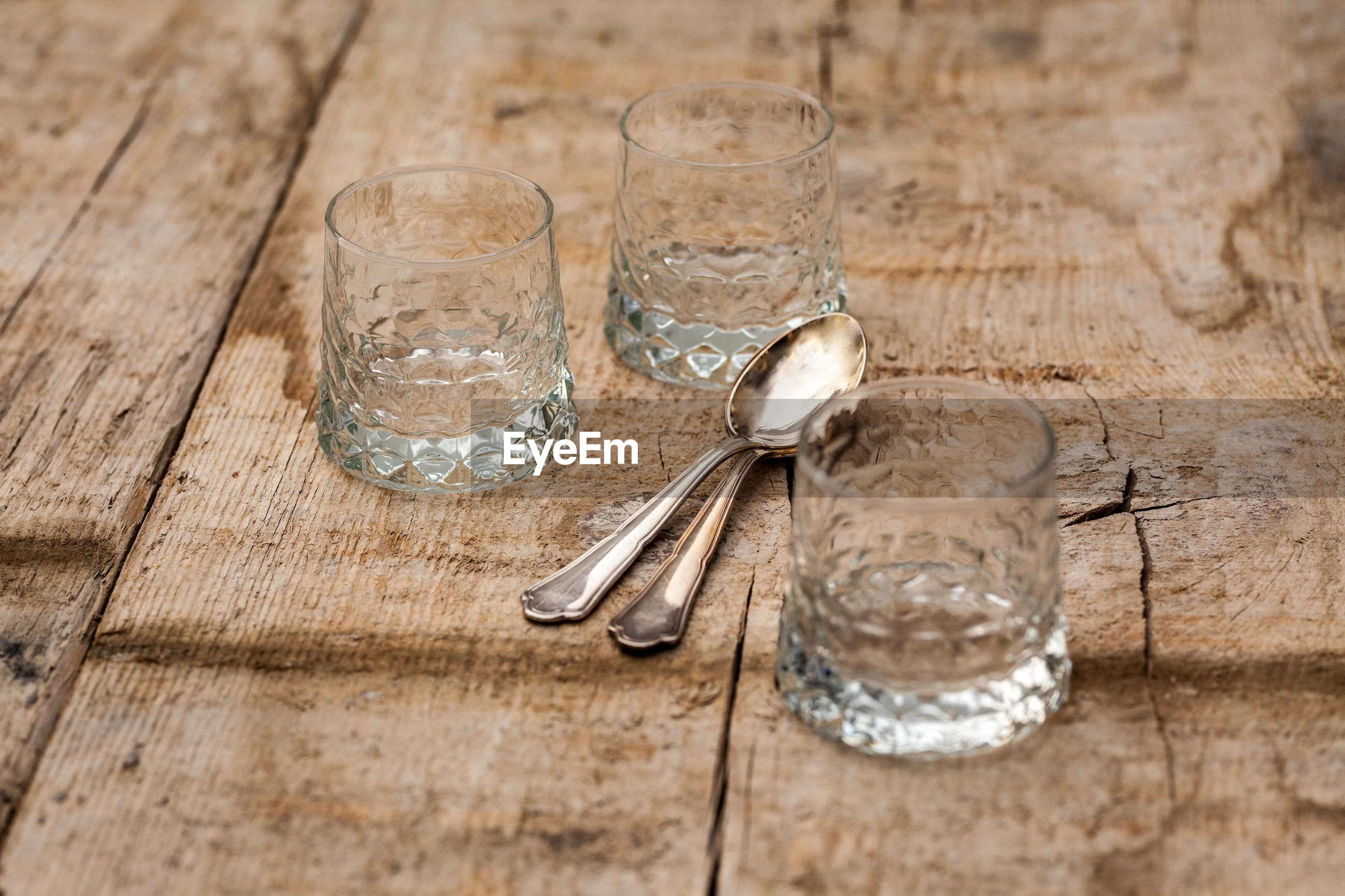 Empty glasses with spoons on wooden table