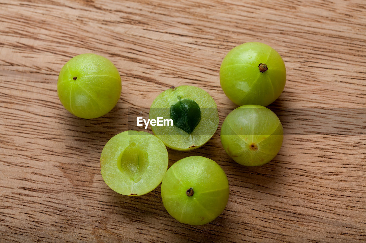 healthy eating, fruit, food and drink, food, wellbeing, table, wood - material, freshness, green color, still life, indoors, no people, high angle view, group of objects, apple - fruit, close-up, granny smith apple, apple, slice, organic
