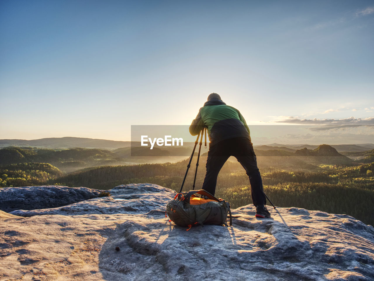 Artist set camera and tripod to photograph the sunrise on a rocky summit. artist works in nature