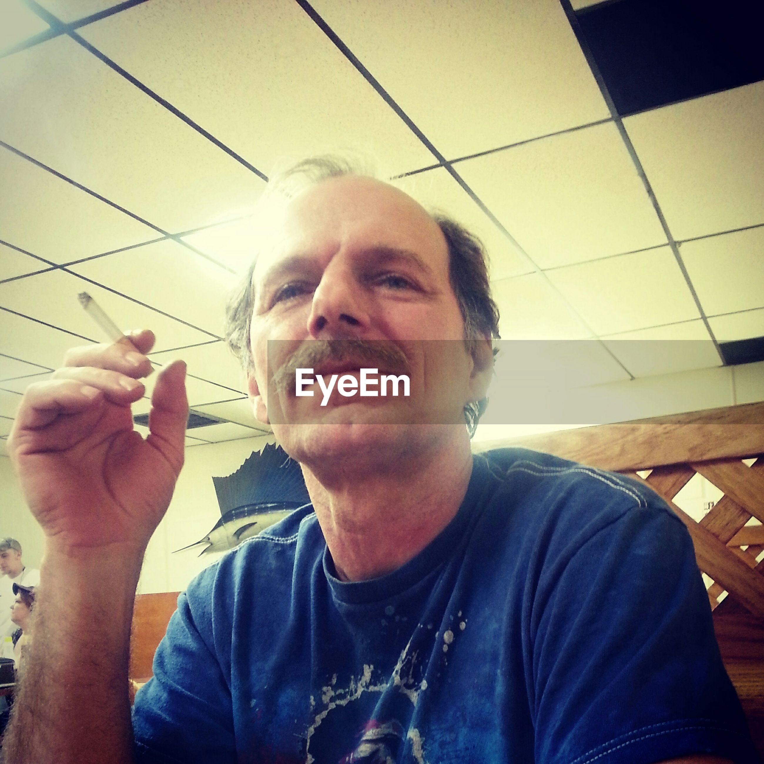 Mature man holding cigarette in restaurant