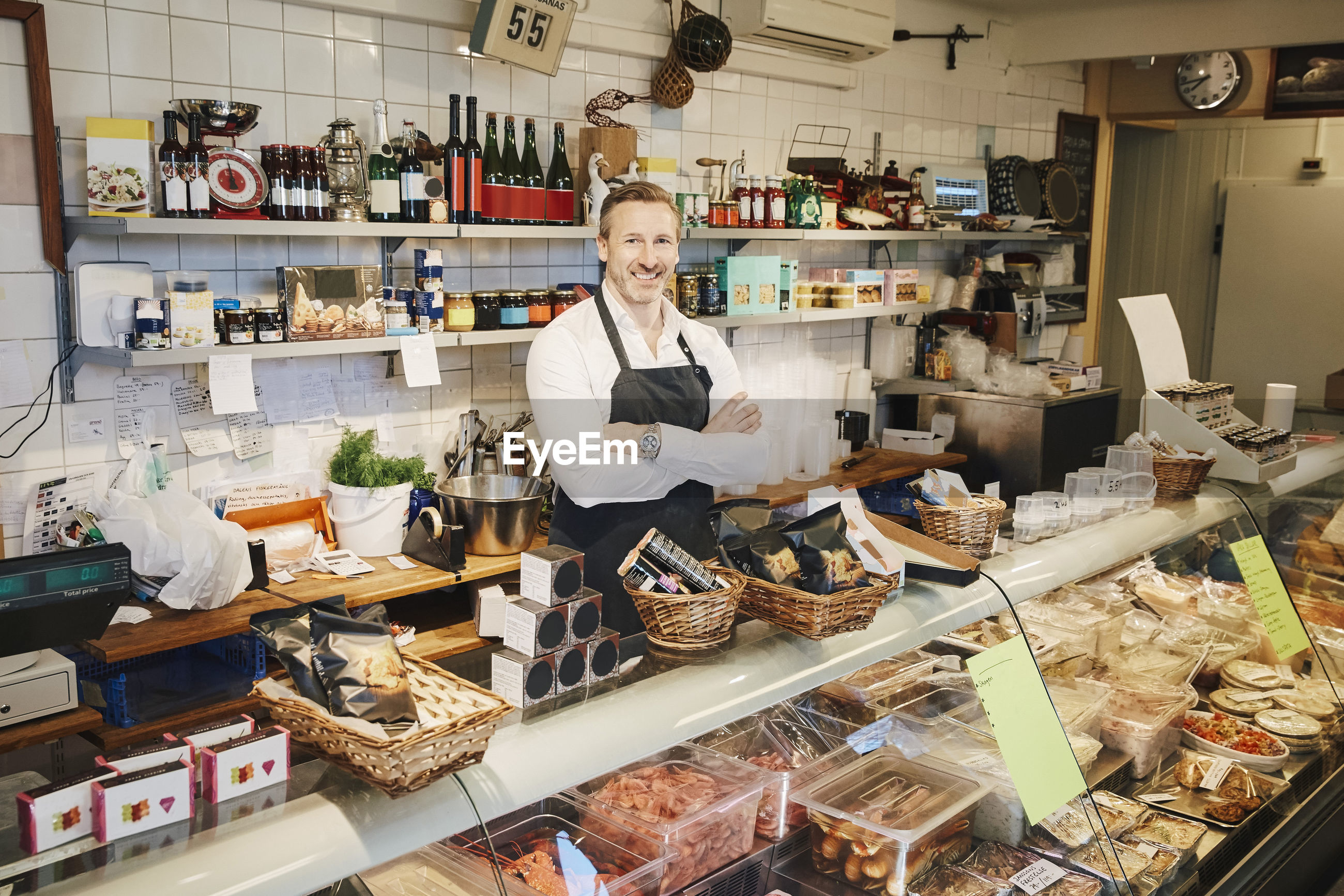 PORTRAIT OF WOMAN STANDING BY STORE