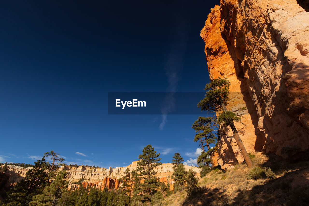 sky, rock, rock - object, rock formation, solid, blue, nature, tranquility, plant, beauty in nature, scenics - nature, no people, tranquil scene, non-urban scene, low angle view, physical geography, mountain, day, geology, sunlight, outdoors, formation, eroded, arid climate