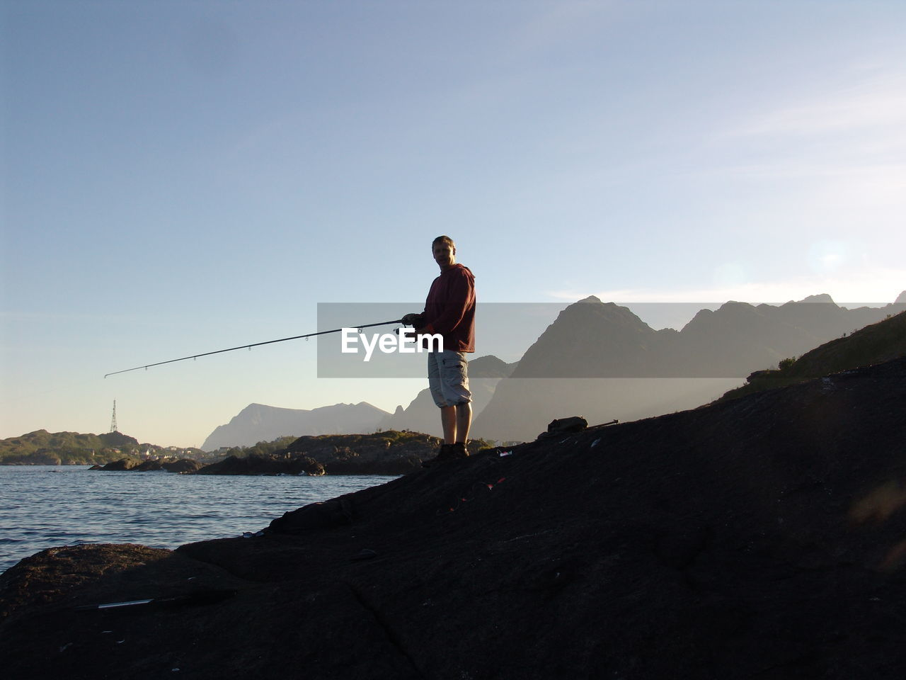 Man fishing at sea shore by mountains against sky