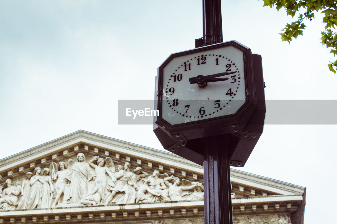 low angle view, clock, sky, time, built structure, accuracy, no people, architecture, day, nature, instrument of time, number, building exterior, clock face, outdoors, cloud - sky, minute hand, communication, clock hand, shape, floral pattern
