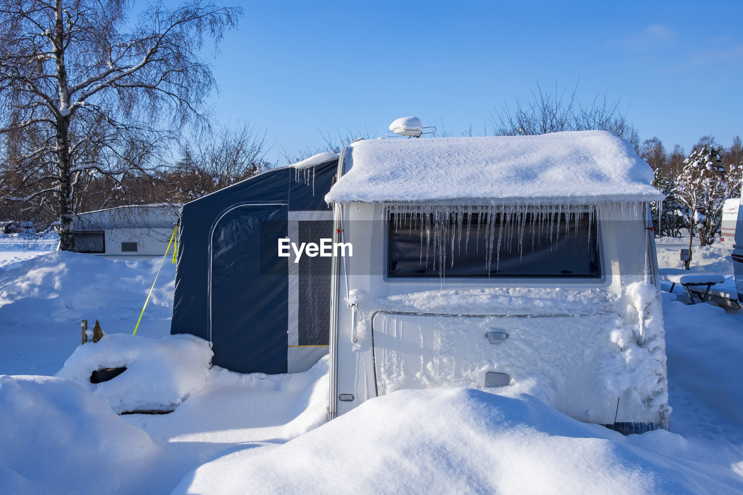 SNOW COVERED HOUSE AGAINST BUILDING