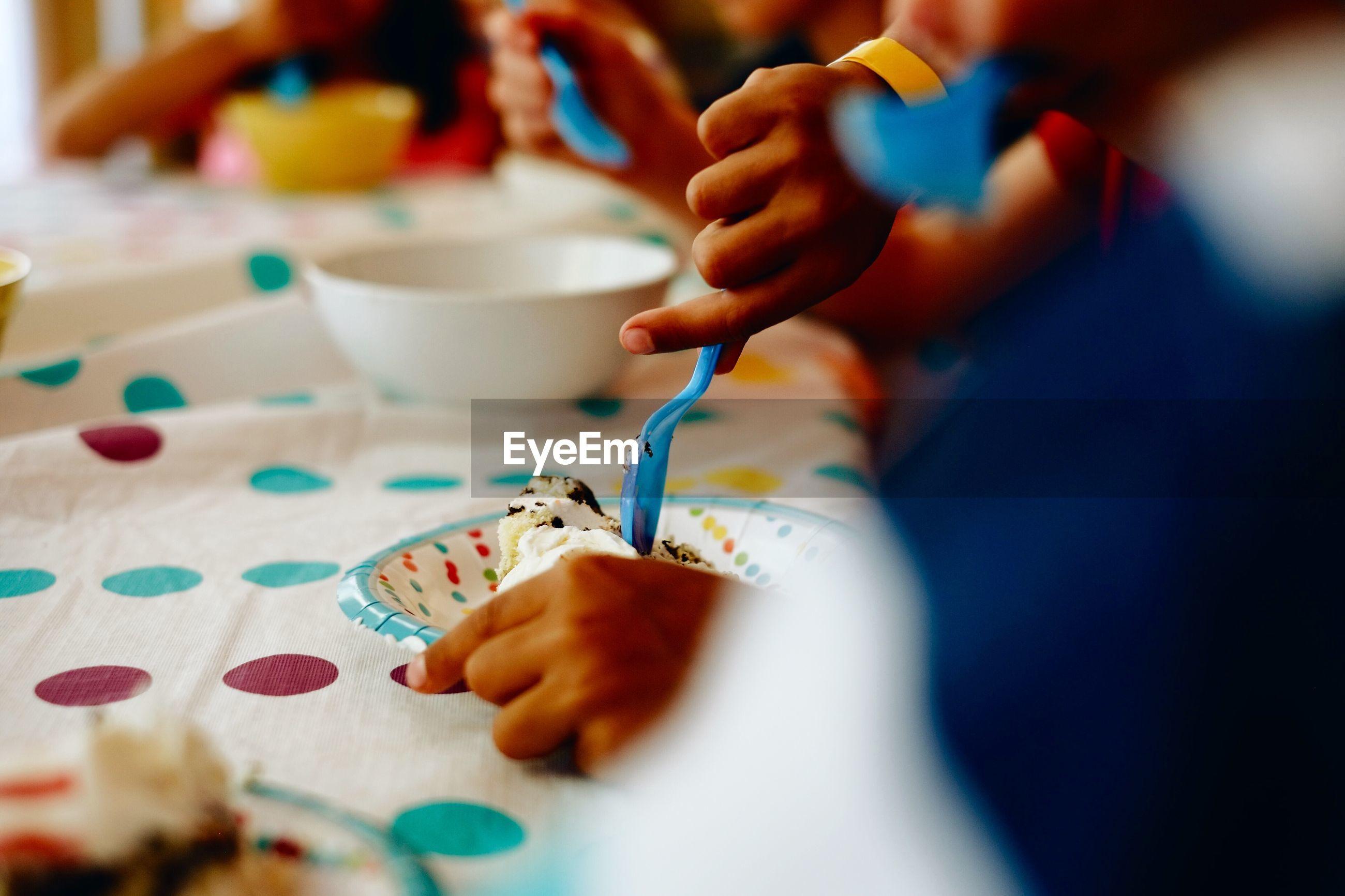 Cropped image of kids eating cake