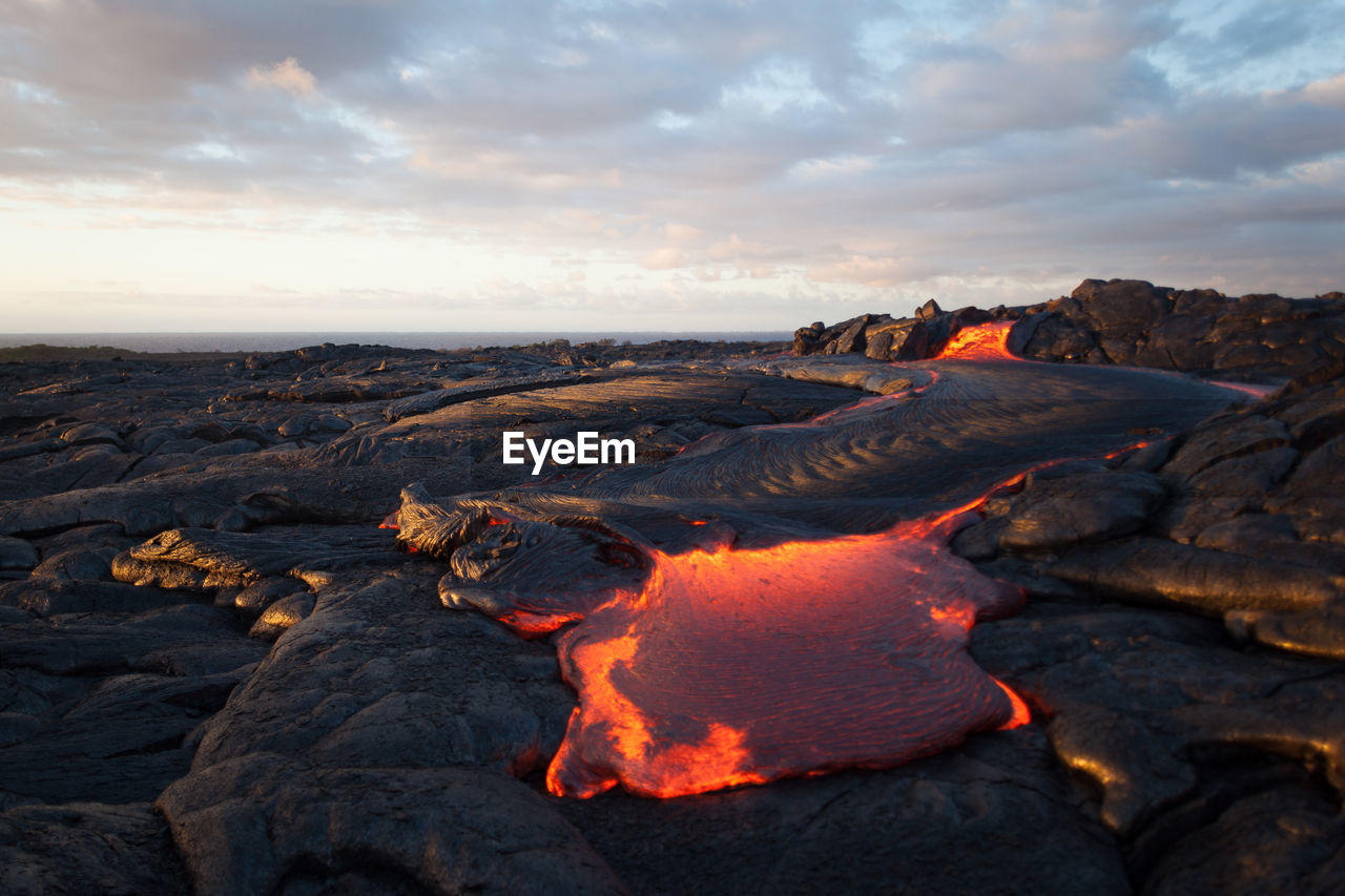 Scenic view of volcano erupting against sky during sunset