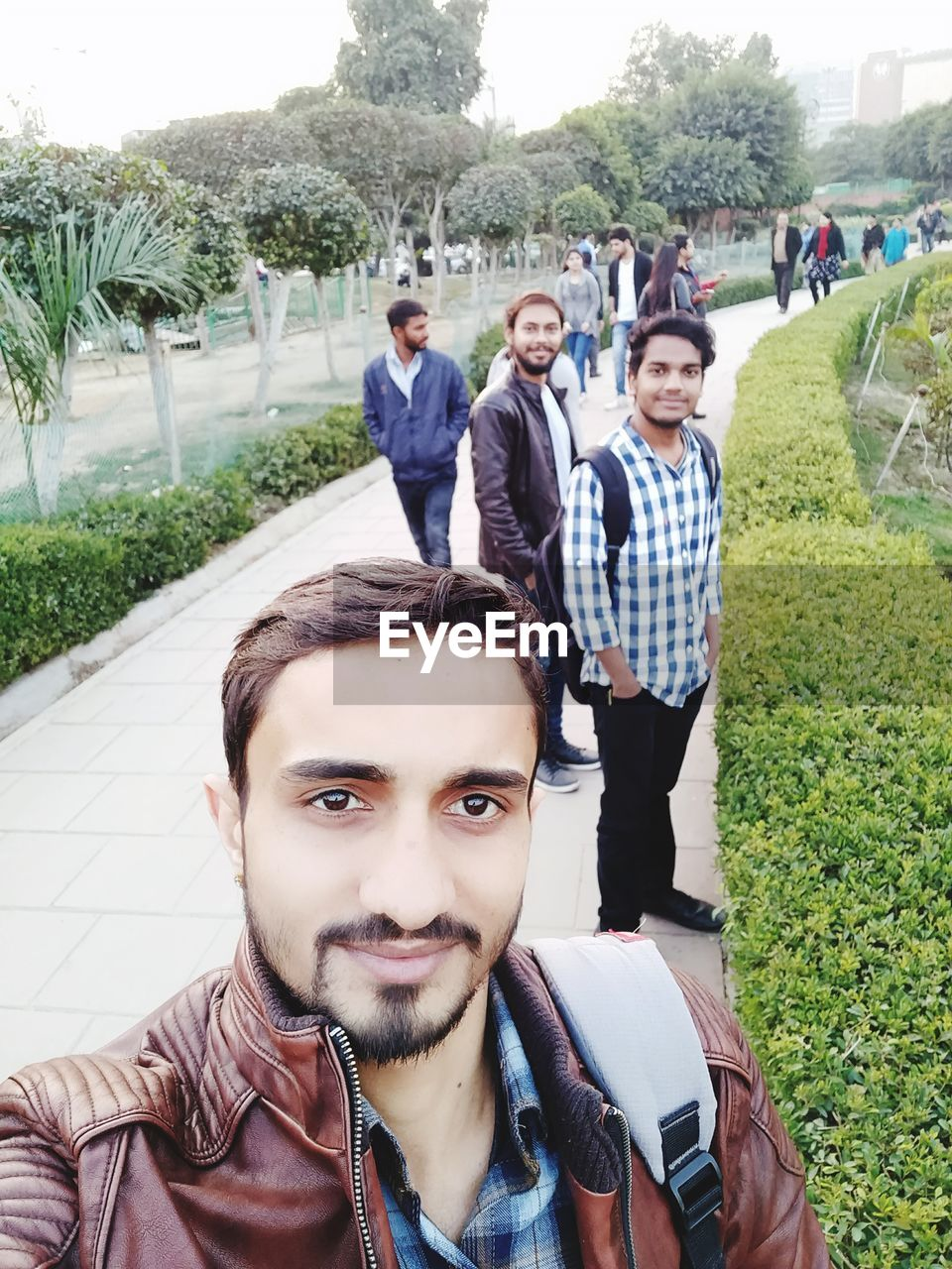 looking at camera, young men, young adult, portrait, real people, young women, mid adult men, front view, lifestyles, day, togetherness, outdoors, leisure activity, smiling, standing, men, happiness, tree, technology, wireless technology, grass, people